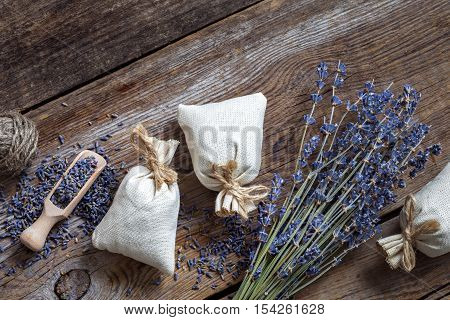Bunch of lavender flowers and three sachets filled with dried lavender. Top view. Flat lay.