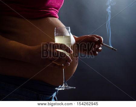 Concept of unhealthy habits during pregnancy. A pregnant woman smoking cigarette and drinking Alcohol and coffee.