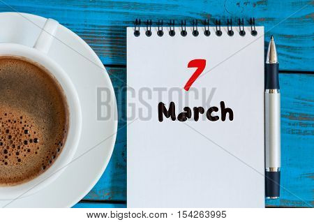 March 7th. Day 7 of month, calendar on blue wooden table background with morning coffee cup. Spring time, Top view.