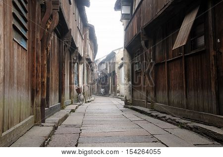 Wooden weathered buildings lining a narrow walkway in tongxiang wuzhen scenic town east view in Zhejiang province China in the early morning mist.