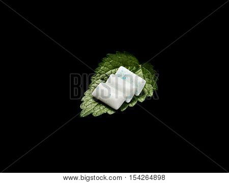 Chewing Gum with Fresh Mint Leaves Isolated on black Background