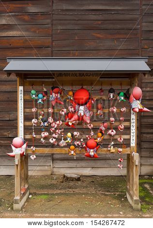 Takayama Japan - September 24 2016: Wooden rack of Sarubobo folk deity in different colors at Hikakokubun-ji Buddhist Temple. Idol is good luck charm. Also called Monkey Child. Dark wooden background.