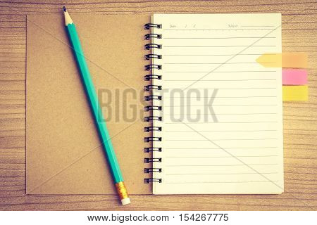 Opened diary book with colorful bookmark on page and pencil with vintage effect