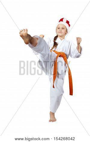 Karateka in the cap of Santa Claus hits a kick leg forward