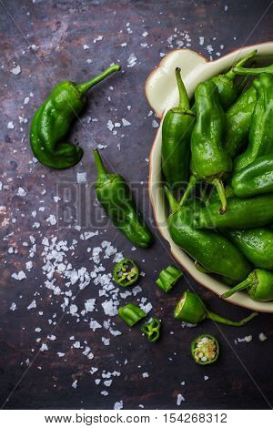Food and drink, still life, moody concept. Raw green mexican spanish peppers jalapeno on a black rusty table. Selective focus, top view flat lay overhead