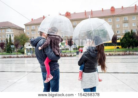 Beautiful young family with two little daughters under the umbrellas, in town on a rainy day. Rear view
