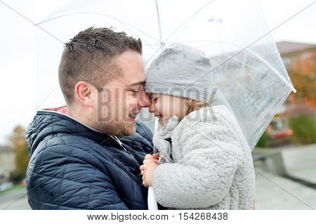Young father holding his little daughter under the umbrella in town on a rainy day.