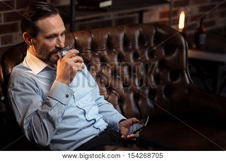 After a working day. Pleasant good looking confident man holding a glass of whisky and taking a sip while relaxing after a working day