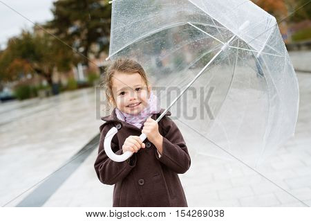 Cute little girl under the transparent umbrella in town on a rainy day.