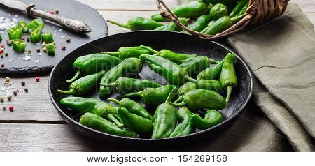Food and drink, still life, moody concept. Raw green peppers pimientos de padron mexican jalapeno traditional spanish tapas on a wooden table. Selective focus