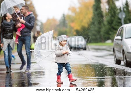 Beautiful young family with two daughters under the umbrellas. Walking in the street on a rainy day.
