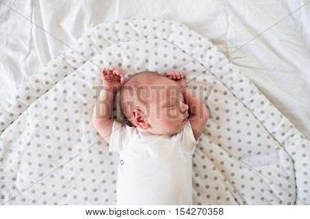 Cute little newborn baby boy lying on bed, sleeping, hands up. Close up.