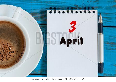 April 3rd. Day 3 of month, calendar with morning coffee cup, at workplace. Spring time, Top view.