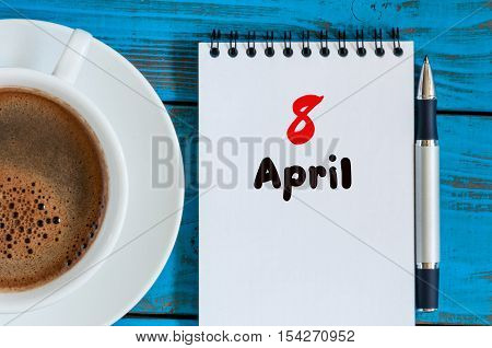 April 8th. Day 8 of month, calendar with morning coffee cup, at workplace. Spring time, Top view.