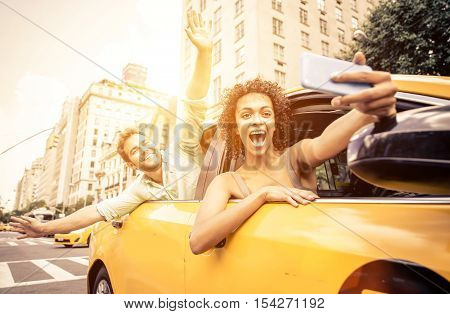 Happy couple driving in New york on a yellow cab and taking selfie with smart phone