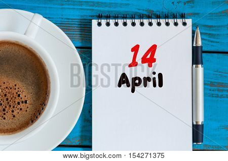 April 14th. Day 14 of month, calendar with morning coffee cup, at workplace. Spring time, Top view.