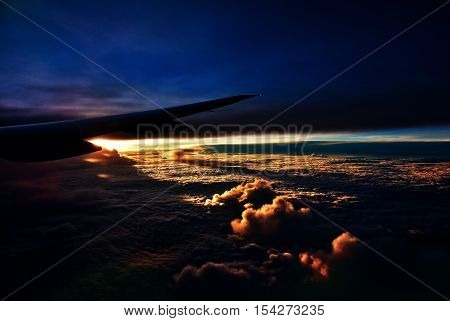August 2015.Fly from Singapore to Houston.View of the right wing passenger aircraft.Below the thick clouds illuminated by the sun.Photo with special dramatic effect.Horizontal view