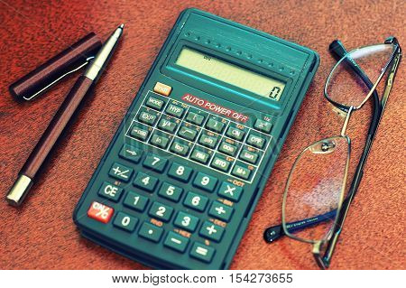 gray business calculator on a wooden table and a stack of money for the calculation of the amount of utility bills payment