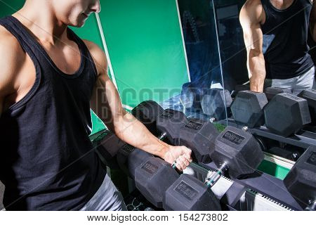 Unrecognizable bodybuilder in black tank holding dumbbell in gym against of mirror