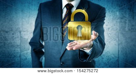 Business man is showing a golden closed padlock in the open palm of his outstretched left hand. Business concept for security privacy secrecy protection safety wealth achievement and success.