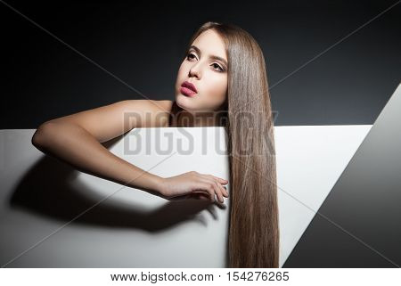 Portrait of young brunette looking away casting arm shadow