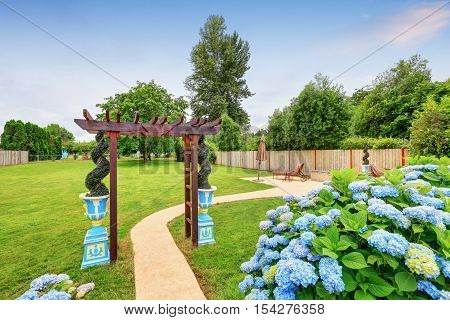 Nicely Decorated Pergola And Blue Flowers In The Backyard