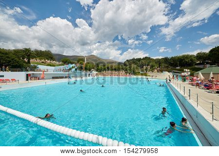 CERIALE, ITALY - AUG 05, 2016: People in swimming pool at aqua-park Caravelle. Aqua-park offers many attractions, including water slides and large swimming pools.