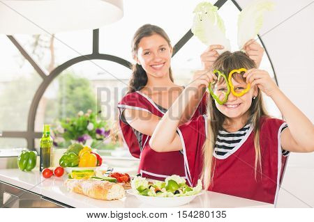 Happy family keeps fresh pieces of bell pepper. Carnival mask. Cooking vegetarian meal at kitchen. Funny sisters making salad. Healthy lifestyle. Recipe of vitamins nutrition. Girls looking at camera