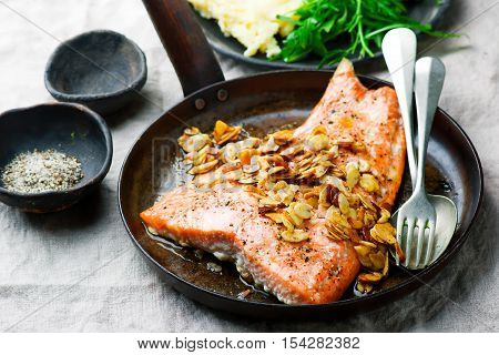 Trout sauted in butter with almonds . Selective focus.Style rustic