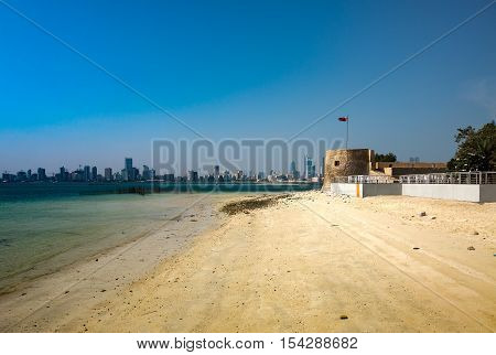 MUHARRAQ, BAHRAIN - OCT 29, 2016: Beautiful view of the Bu Maher Fort with the beach and Manama city in the background