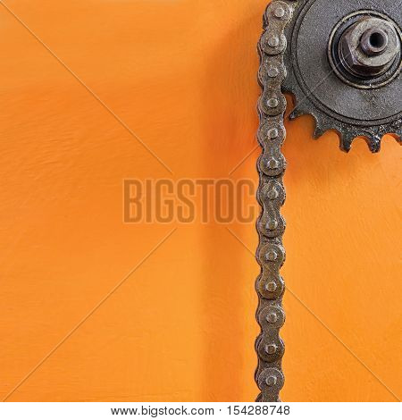 Metal cogwheel and black chain on orange background with empty space for text.