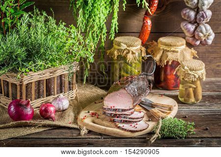 Rural smokehouse ham preparation for smoking on old wooden table