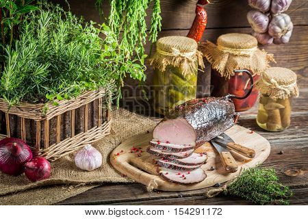 Pantry with preserves and smoked ham on old wooden table