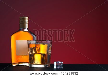 Whiskey on the rocks in glass and whiskey bottle on red background