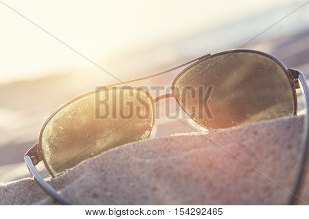 Sunglasses on sand at sunset, beach and ocean in the background. Vacation theme.