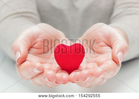 Small red heart in woman's hands in a gesture of giving, protecting. Health, life, love symbol.