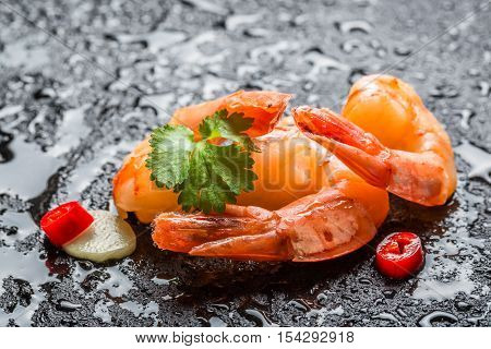 Shrimps served on a wet rock on black rock