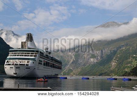 Large white cruise ship in Geirangerfjord Norway