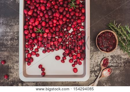 Fresh cranberries and cranberry jam  placed on a rustic surface. Top view, blank space