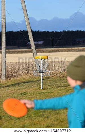 Young woman aiming disc on disc golf course. Focus in target.