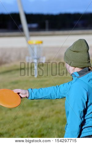 Young woman aiming disc on disc golf course. Focus in person.