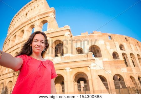 Back view of young woman in front of colosseum in rome, italy