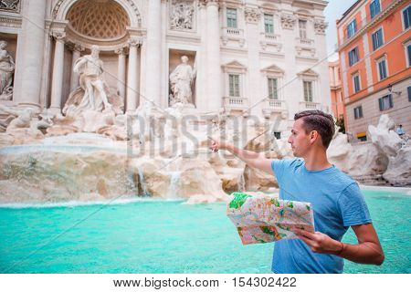 Caucasian boy near fountain Fontana di Trevi with city map