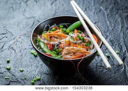 Noodles with vegetables and prawns on black rock