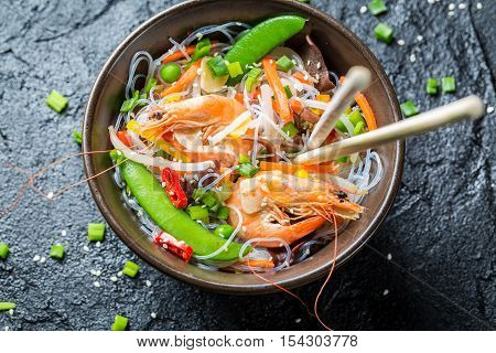 Traditional dish with shrimp and noodles on black rock