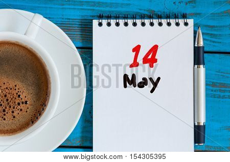 May 14th. Day 14 of month, calendar on white notepad with morning coffee cup at work place background. Spring time, Top view.