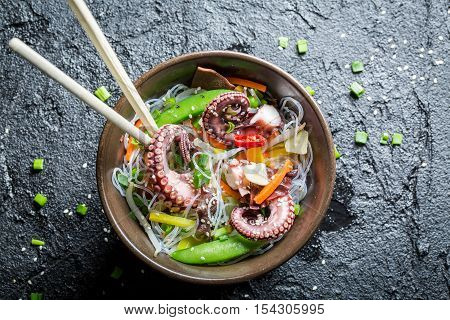 Vegetables with noodles and octopus on black rock