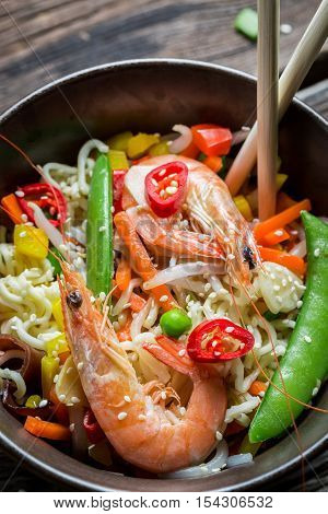Shrimp with vegetables and noodles on old wooden table