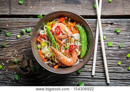 Chinese noodles with vegetables and prawns on old wooden table