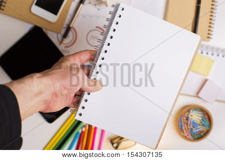 Male hand holding blank white spiral notepad above office desktop with blurry electronic devices and other stationery items. Mock up
